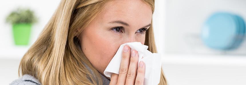 Frau putzt sich die Nase: Aspirin® Complex kann verstopfte Nasen und Nebenhöhlen befreien.