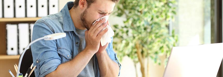 Ein Mann hat sich mit einer Erkältung angesteckt und schnäuzt sich.