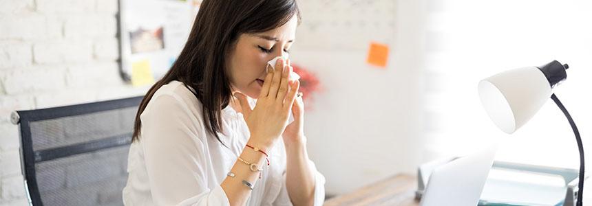 Eine Frau ist erkältet in der Arbeit und schnäuzt sich.