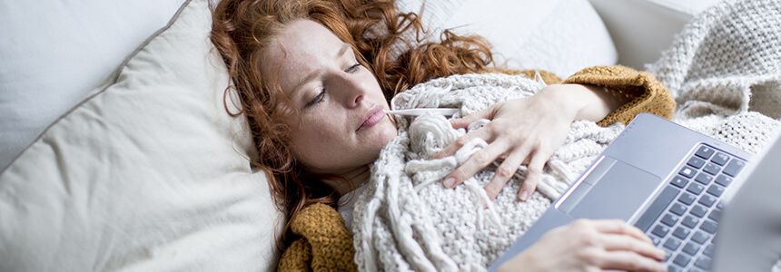Eine Frau liegt wegen Erkältung oder Grippe krank im Bett.