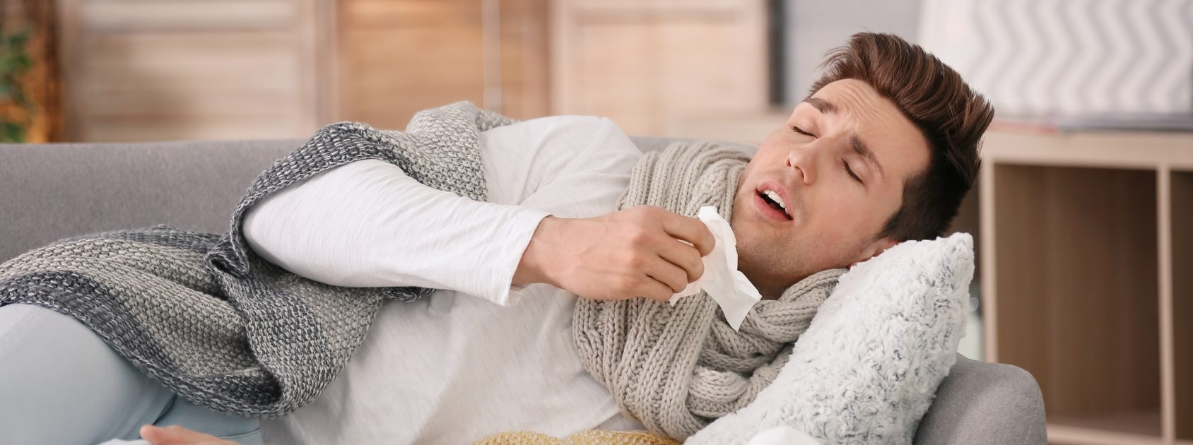 Viraler Infekt: Mann liegt mit Erkältung am Sofa