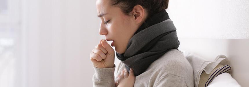 Frau hält sich bei Husten die Hand vor den Mund