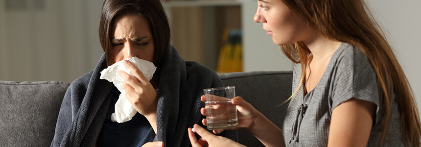 Zur Behandlung der Grippe ist für diese Frau viel Trinken wichtig – besonders, wenn das Thermometer eine erhöhte Temperatur anzeigt.