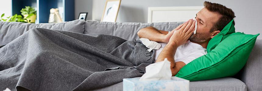 Mann liegt mit andauerndem Erkältungsverlauf auf dem Sofa