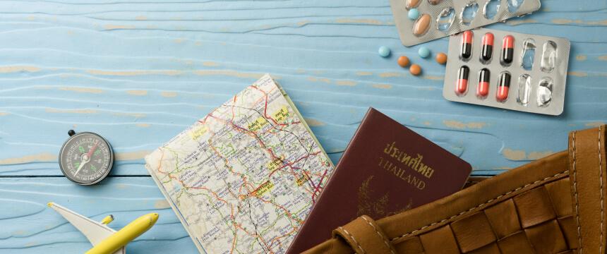 Eine Landkarte, ein Reisepass und Tabletten auf einem Tisch.
