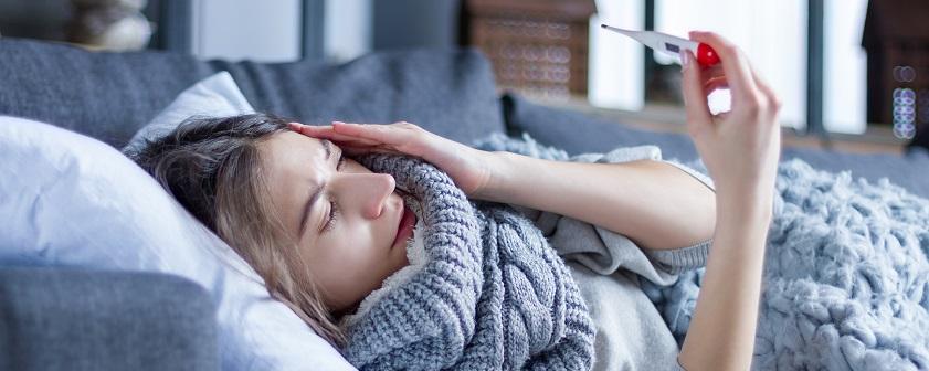 Wegen einer Erkältung schwitzt eine Frau und liegt im Bett.