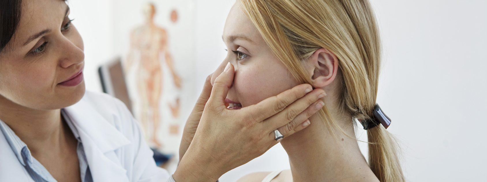 Frau mit akuten Sinusitis-Anzeichen lässt sich beim Arzt untersuchen