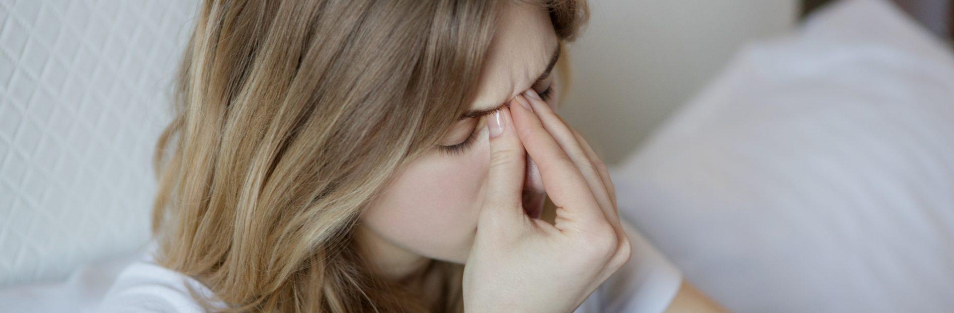 Frau mit Kieferhöhlenentzündung fasst sich an den schmerzenden Nasenbereich.