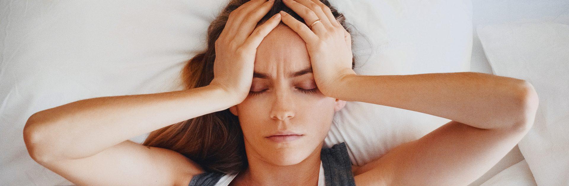 Frau mit Pansinusitis hält sich den schmerzenden Kopf.