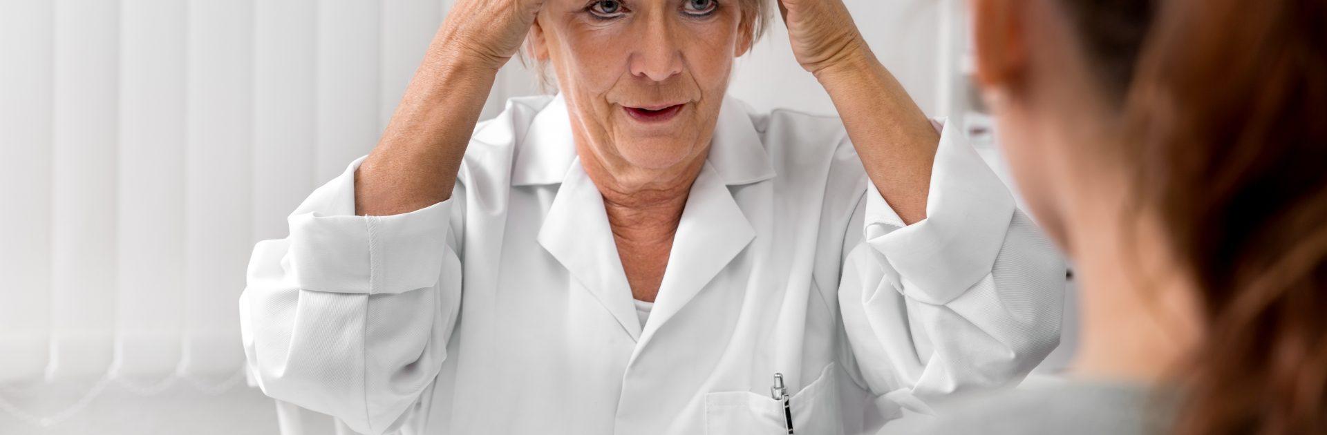 Ärztin deutet auf ihre Stirn, um einer Patientin die Lokalisation der Stirnhöhlenentzündung zu veranschaulichen.