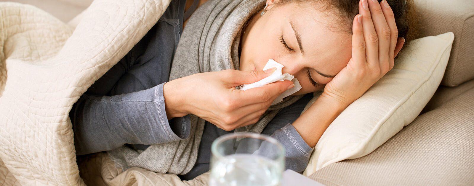 Eine sich schnäuzende Frau liegt müde und schlapp mit Erkältung auf dem Sofa.
