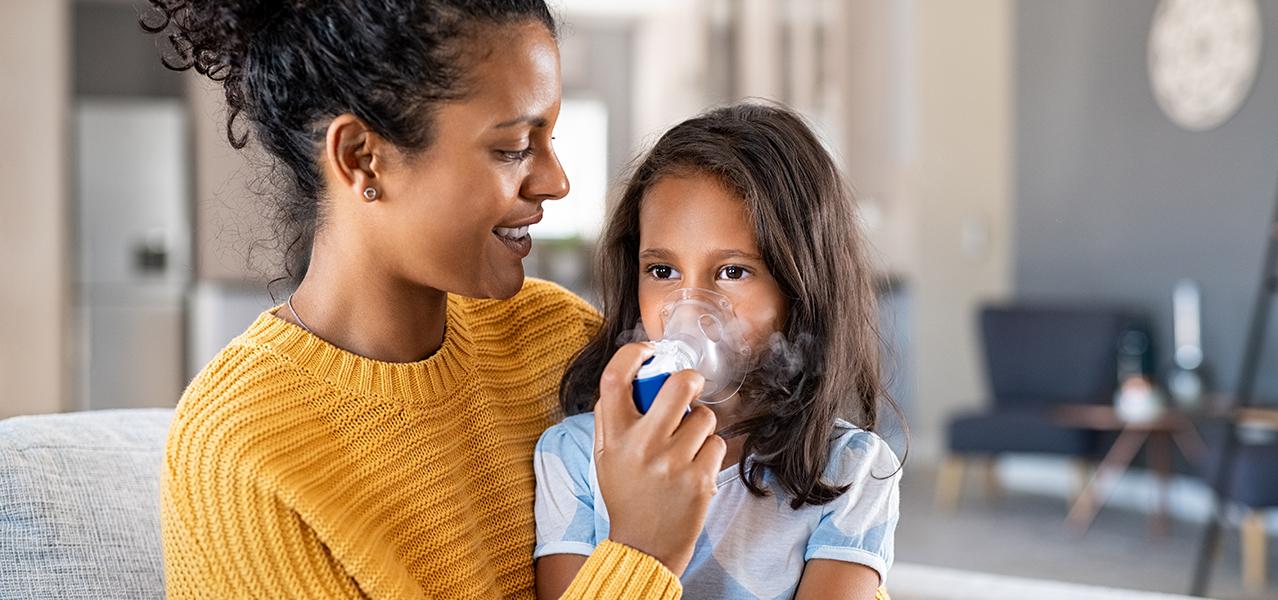 Mutter hilft ihrem erkälteten Kind beim Inhalieren.